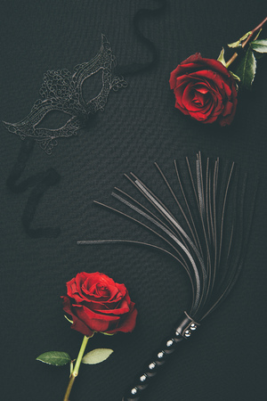 Black whip and lacy mask with rose flowers isolated on black