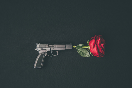 Red rose shooting from gun isolated on black Stock Photo