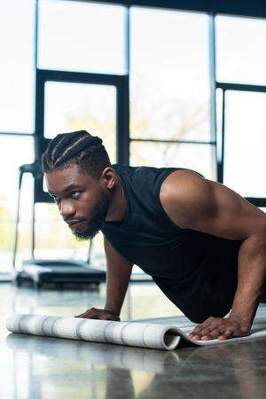 focused muscular african american man doing push ups in gym Stock Photo