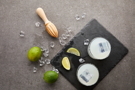 flat lay with wooden squeezer, refreshing sour caipirinha cocktails with lime and ice on grey tabletop
