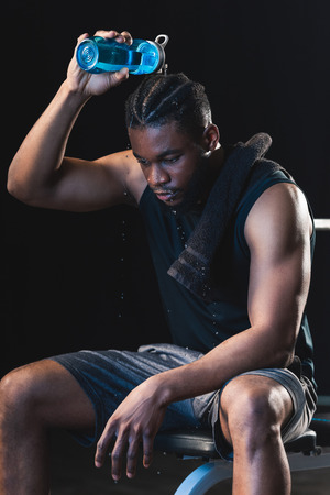 tired african american sportsman pouring water on head while sitting after workout in gym