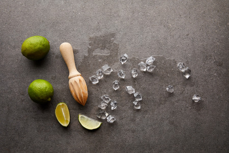 flat lay with wooden squeezer, limes and ice cubes for cocktail on grey surface Stockfoto
