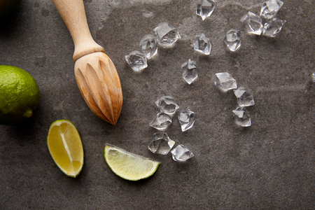 flat lay with wooden squeezer, lime pieces and ice cubes for cocktail on grey surface