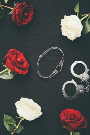 Collar and handcuffs with rose flowers isolated on black