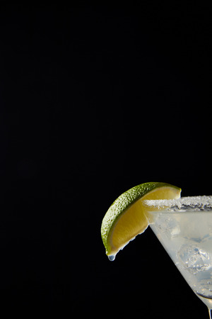 Close up view of cold margarita cocktail with lime isolated on black 写真素材