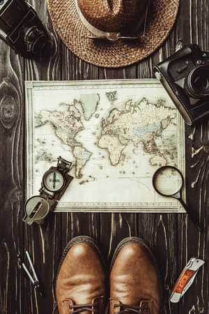 top view of travel setting with straw hat, map, shoes, compass, magnifying glass and photo cameras on dark wooden surface Stok Fotoğraf