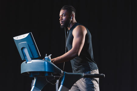 handsome young african american man in earphones exercising on treadmill and looking away Stockfoto