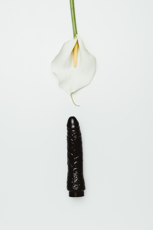 Black dildo with white calla flower isolated on white