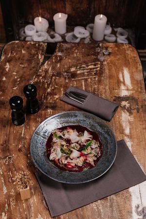 delicious Ceviche with Dorado and daikon on wooden table Stock Photo