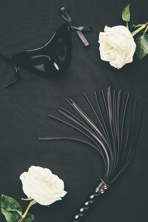 Black flogging whip and mask with white roses isolated on black Stock Photo