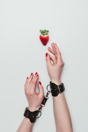 Female hands tied with leather handcuffs reaching for strawberry isolated on white Stock Photo