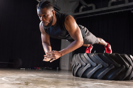 muscular african american sportsman exercising with tyre Stock Photo