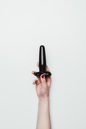 Schwarzer Butt Plug in weiblicher Hand lokalisiert auf Weiß