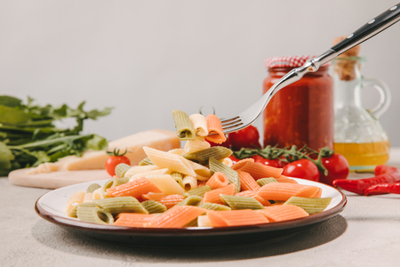 fork with pierced colorful pasta above plate on concrete tabletop with various food on background