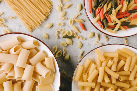 top view of different raw pasta in bowls on messy concrete surface 스톡 콘텐츠