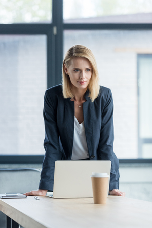 attractive blonde businesswoman leaning at table with laptop in office Stock Photo