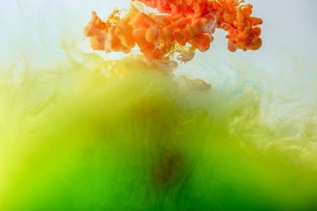 acrylic background with mixing green, yellow and orange paint in water 写真素材