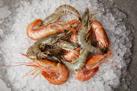 top view of heap of raw and cooked prawns on crushed ice