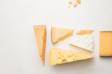 Top view of different types of cheese on white