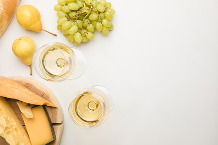 Top view of different types of cheese on wooden board, wineglasses and fruits on white