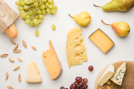 Top view of different types of cheese, grapes, pears, almond and baguette on white 写真素材
