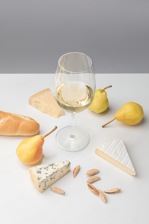 Elevated view of wine glass surrounded by pears, almond, baguette and different types of cheese on gray Reklamní fotografie