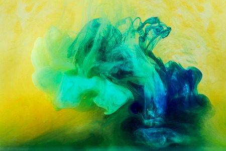 background with green paint flowing in yellow water