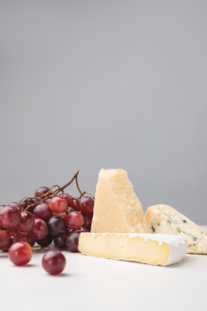 Brie, cheddar and blue cheese with grapes on gray