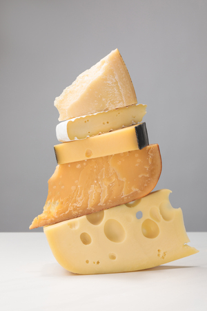 Close up view of stack of different types of cheese on gray