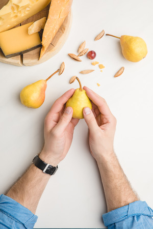 Cropped image of man with pear, almond and different types of cheese on wooden board on white Фото со стока