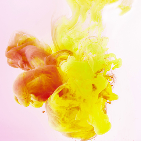 artistic background with flowing yellow and red paint on pink