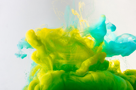 design with flowing turquoise, yellow and green paint in water, isolated on grey Banco de Imagens