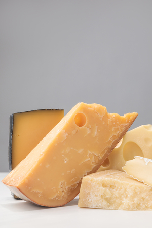 Close up shot of different types of cheese on gray 写真素材