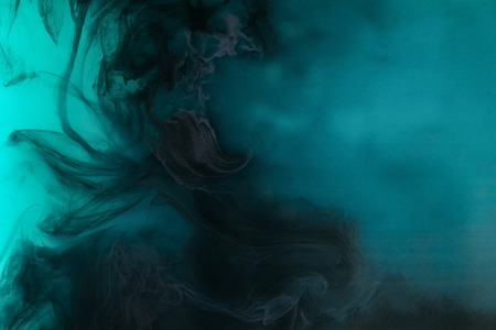 abstract background with black watercolor paint in turquoise water 版權商用圖片