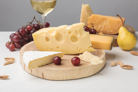 Different types of cheese on wooden boards, wine glass, fruits and almond on gray 版權商用圖片
