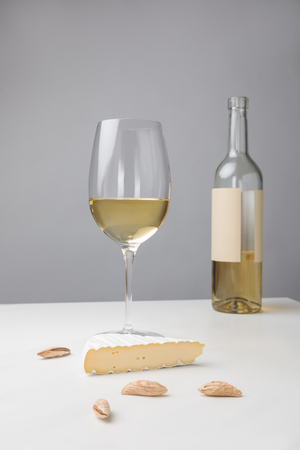 Closeup view of brie cheese, almond, wine glass and bottle on gray Фото со стока