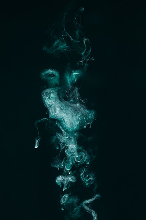abstract magic background with turquoise paint on black