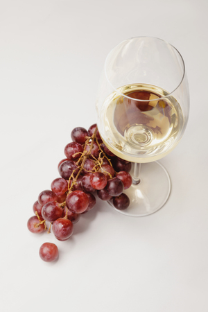 Top view of white wine glass and grapes on white
