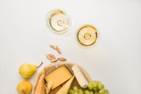 Top view of different types of cheese on wooden board, wine glasses, almond and fruits on white Stock Photo