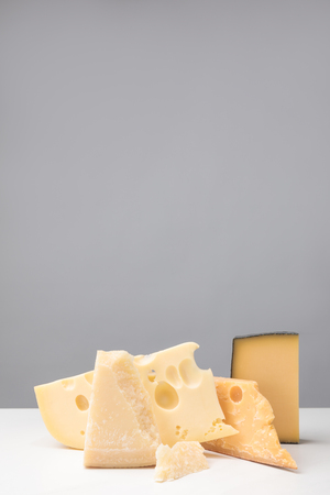Closeup view of different types of cheese on gray Фото со стока