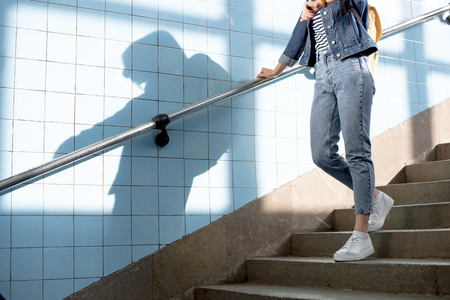 cropped shot of female traveler with backpack going downstairs at subway Stock Photo