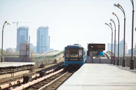 arriving train at outdoor subway station with buildings on background