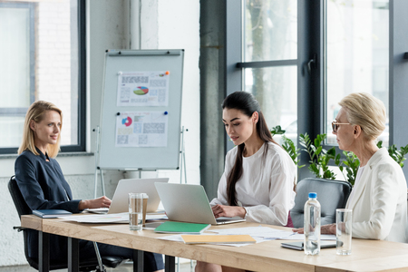beautiful businesswomen using laptops at meeting in office Stock Photo