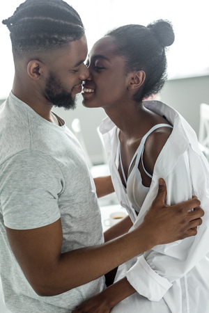 side view of smiling african american boyfriend kissing girlfriend at kitchen 스톡 콘텐츠