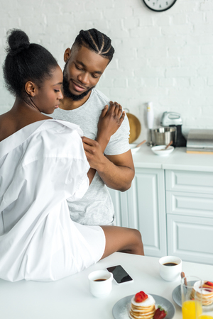 smiling african american boyfriend undressing girlfriend at kitchen