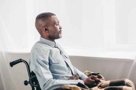 side view of senior african american man sitting in wheelchair and looking away 版權商用圖片 - 106689936