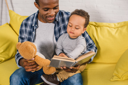 cropped shot of smiling father holding teddy bear and reading book to little son Stock Photo