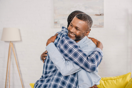 happy senior father and adult son hugging at home