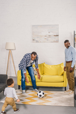 happy father, grandfather and little son playing with soccer ball at home