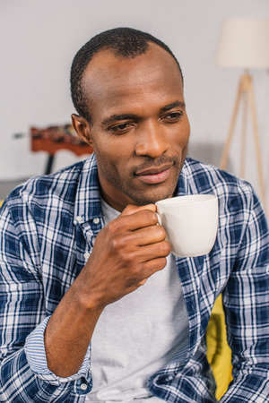 pensive young african american man holding coffee cup at home